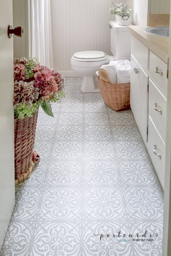 A bathroom with linoleum floors that have been painted using a stencil in gray and white and a basket with flowers sitting on the wall opposite the vanity.