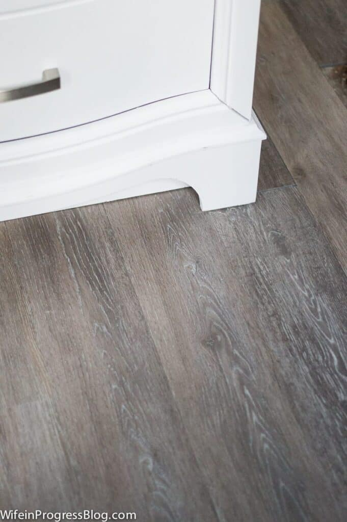 Wood looking luxury vinyl plank floors win a gray color with touches of white in the grain of the wood.