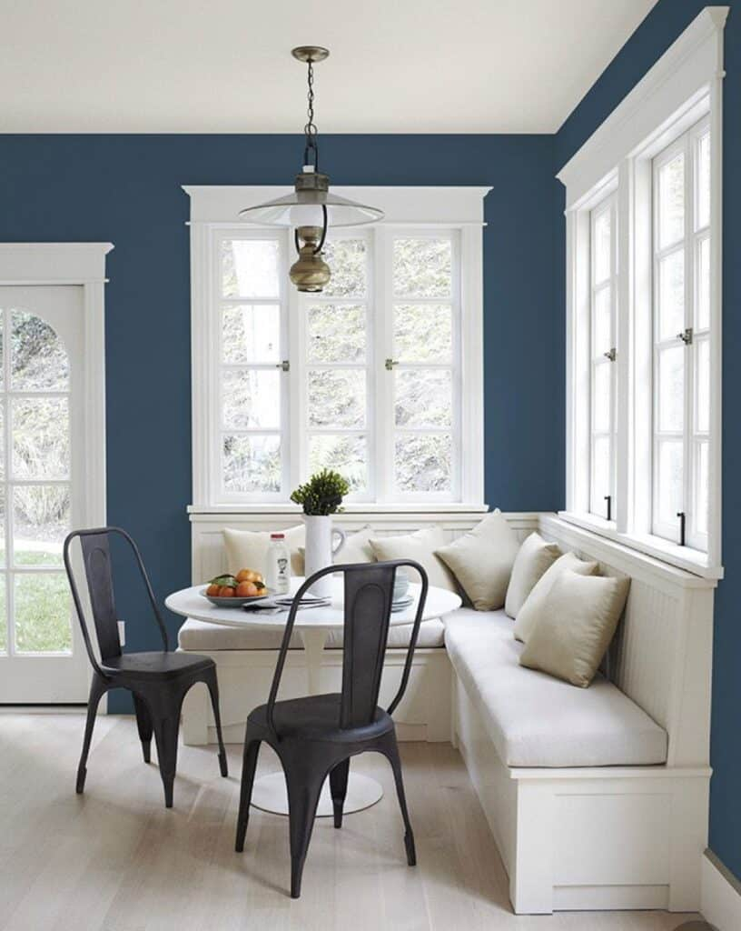 Sherwin Williams Salty Dog on the walls of a breakfast nook.  There is white trim on the windows and a white banquette.