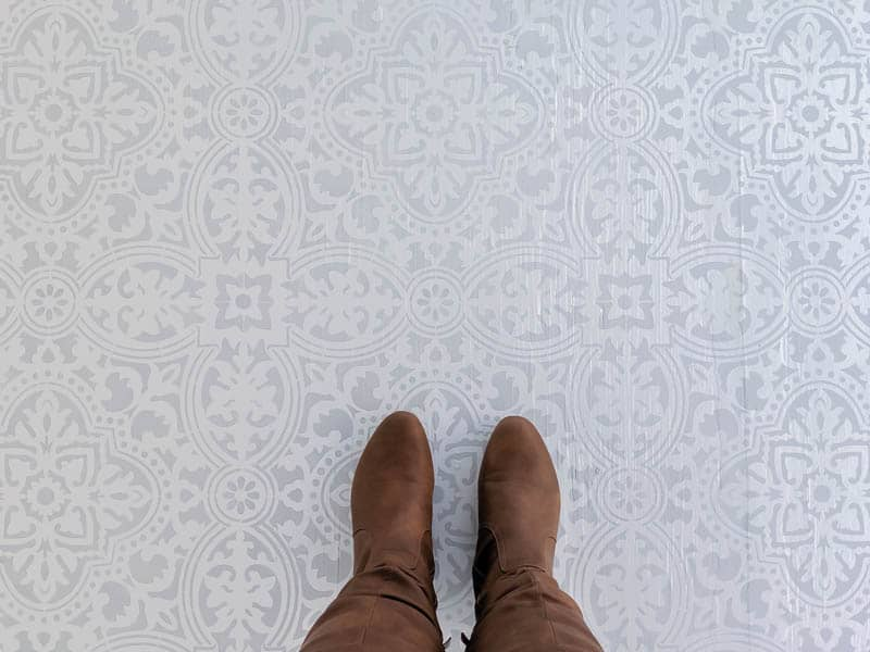 Plywood floors that have been painted using a stencil in gray and white and someone standing on them with brown boots.