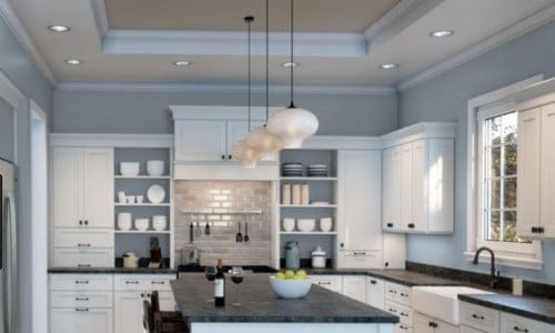Icy used in a kitchen with white cabinetry and black countertops.