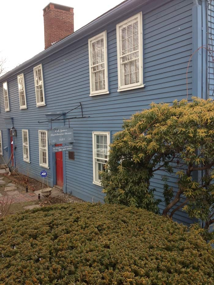 Bachelor Blue used on exterior siding of a two story home with a red door and white trim on the windows.