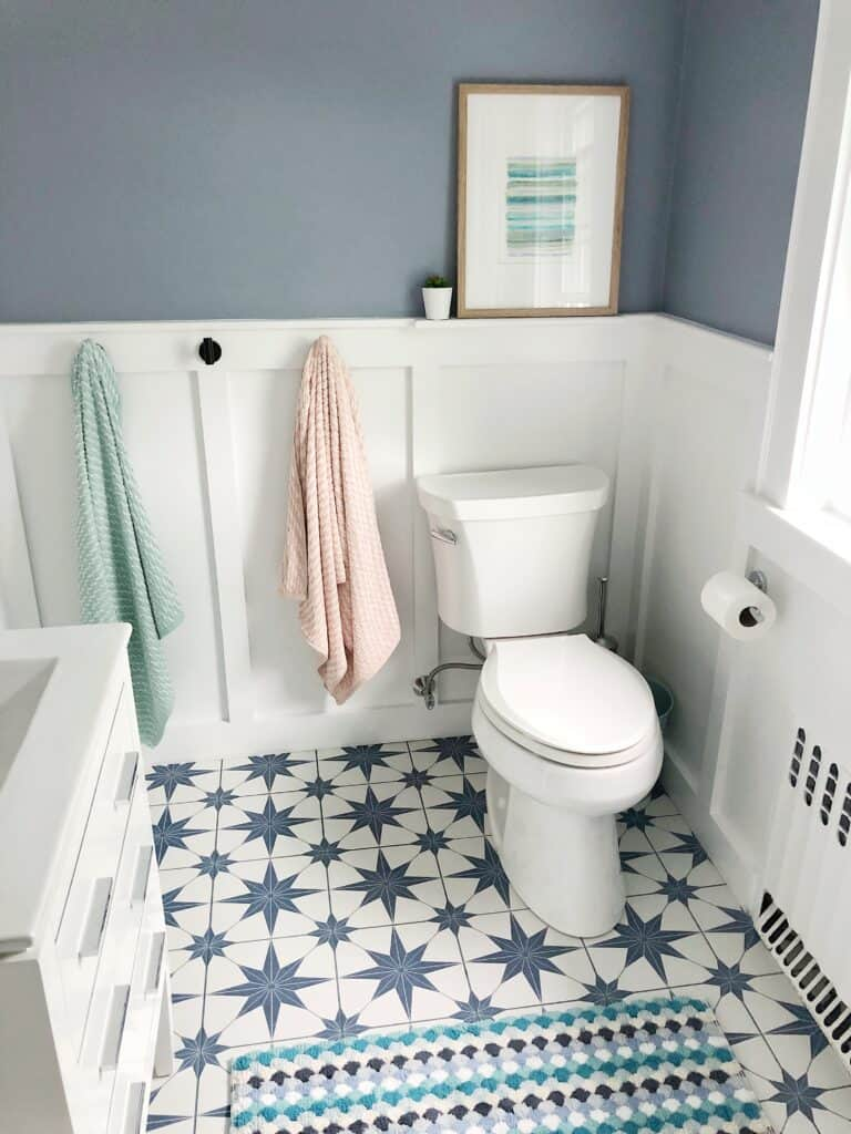 A bathroom with Comet on the walls above white board and batten and there is a star burst shaped tile on the floor.