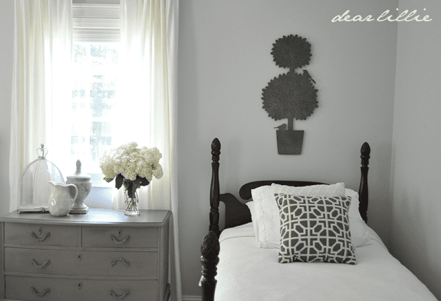 Pebble Beach is on the walls of a bedroom with two wood twin beds and a medium gray dresser in between.
