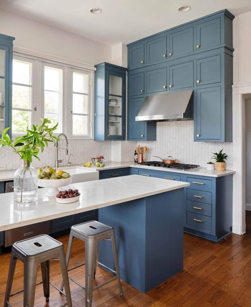 Stillwater is used on kitchen cabinetry with gold hardware and white countertops.