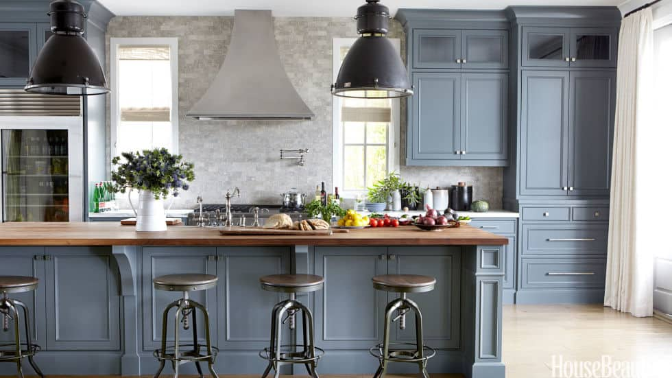 Van Courtland Blue is used on the cabinets of a kitchen with wood countertops and marble backsplash.