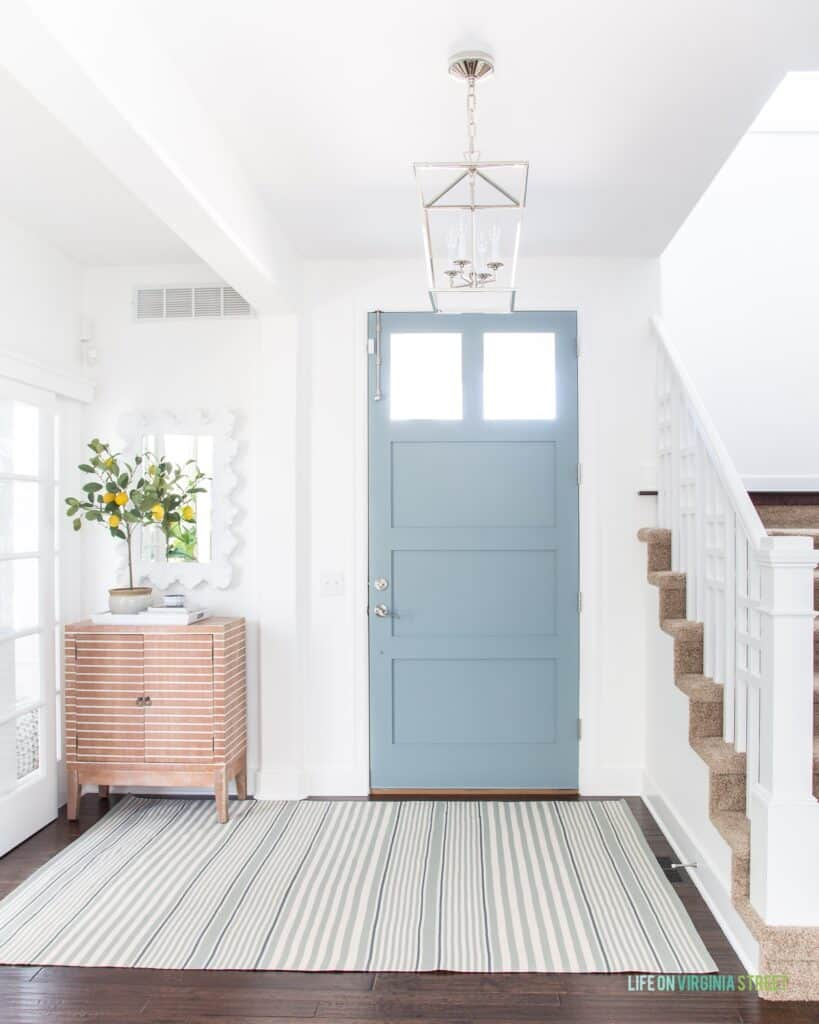 The inside fo the front door painted in Waters Edge with white walls, a striped rug and dark hardwood floors.